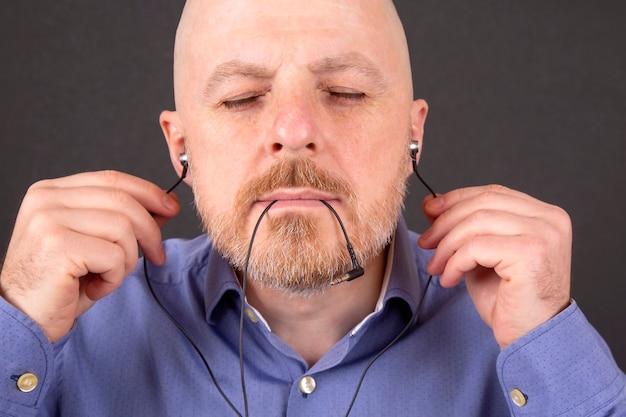 あごひげを生やした男は真空ヘッドホンで音楽を聴きたい