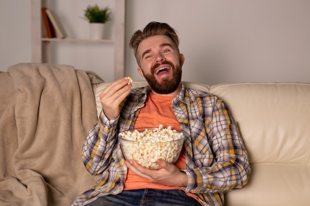 Бородатый мужчина смотрит фильм или спортивные игры по телевизору, ест попкорн в доме ночью. кино, чемпионат и концепция досуга.