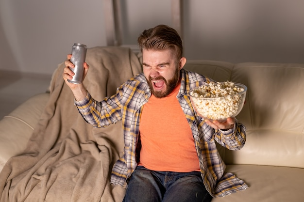 夜、家の中でポップコーンを食べる映画やスポーツ ゲームのテレビを見ているひげを生やした男。シネマ、チャンピオンシップ、レジャーのコンセプト。