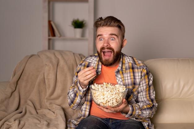Бородатый мужчина смотрит фильм или спортивные игры по телевизору, ест попкорн в доме на ночном чемпионате кино и