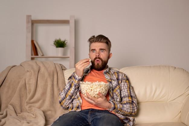 밤에 집에서 팝콘을 먹고 영화 또는 스포츠 게임 tv를보고 수염 난된 남자. 영화, 우승
