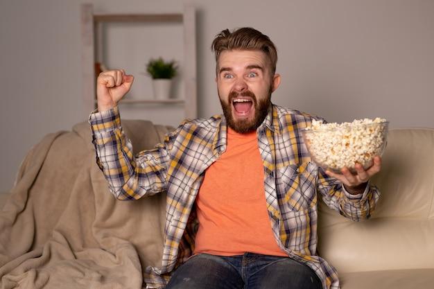 Бородатый мужчина смотрит фильм или спортивные игры по телевизору, ест попкорн в доме ночью. кино, чемпионат