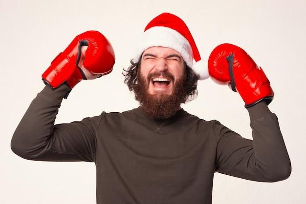 크리스마스 모자와 권투 글러브를 쓴 수염 난 남자가 승자 제스처를 하고 있다.