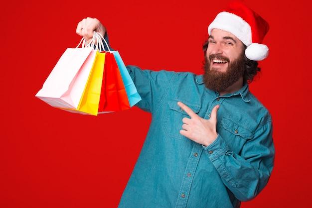 크리스마스 모자를 쓰고 수염 난 남자가 구입 한 선물에 대해 행복합니다.