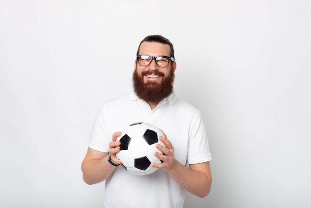 Бородатый мужчина в очках держит футбольный мяч и улыбается в камеру.