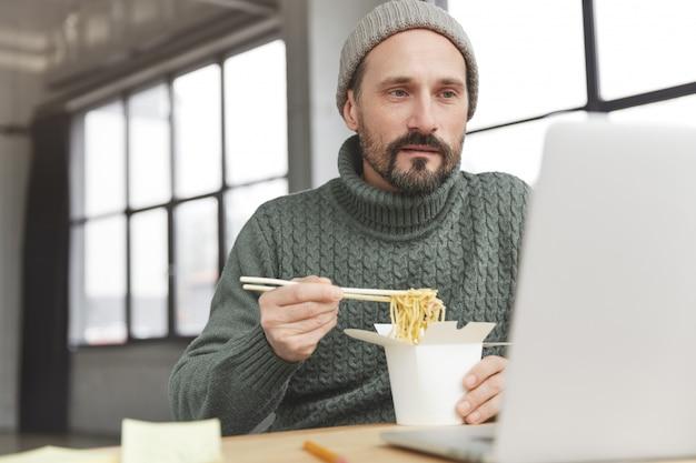 Uomo barbuto che indossa un maglione caldo lavorato a maglia e cappello a pranzo