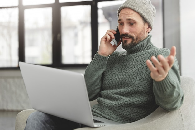 Uomo barbuto che indossa cappello e maglione caldo lavorato a maglia