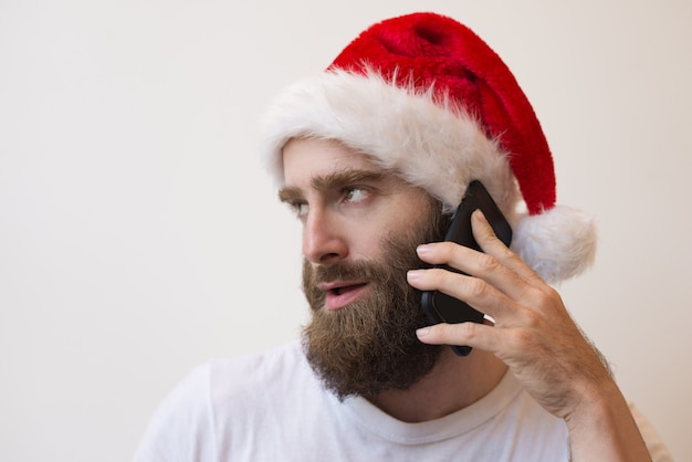 Bearded man wearing santa hat and talking on phone