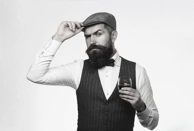 スーツを着てウイスキー、ブランデー、コニャックを飲むひげを生やした男。ひげを生やしたウイスキーのグラス。ソムリエは高価な飲み物を味わいます。飲み物のガラスとジャケットのハンサムな男。黒と白。