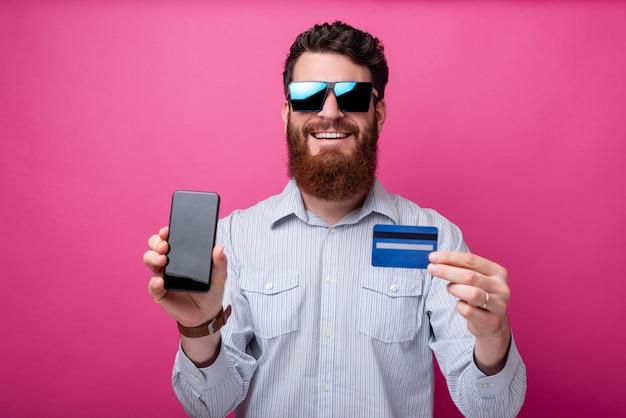 サングラスを身に着けているひげを生やした男は、ピンクの背景に空白の画面とクレジットカードを持つ彼の携帯電話をカメラに見せています。