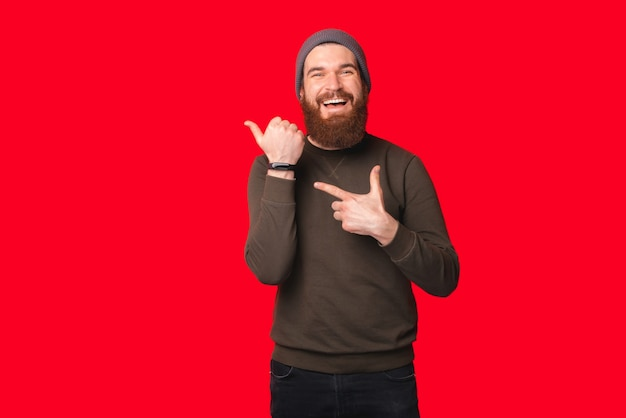 Bearded man wearing warm hat and sweater is pointing at his wrist watch.