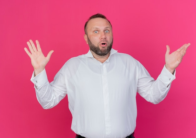 Uomo barbuto che indossa una camicia bianca confuso e incerto alzando le mani in piedi sopra il muro rosa