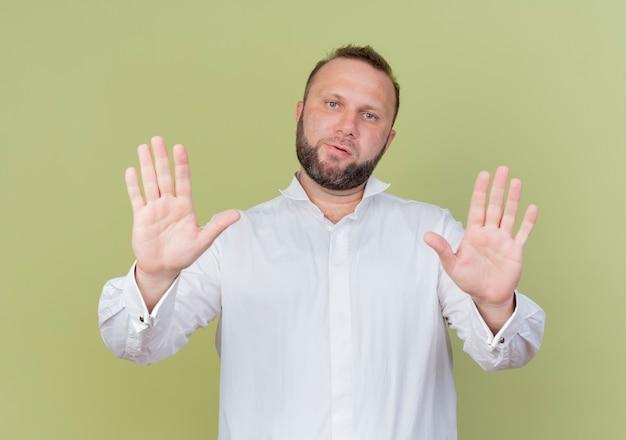 白いシャツを着たひげを生やした男は、軽い壁の上に立っている開いた手のひらで停止ジェスチャーをすることに不満を持っています