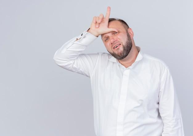 흰 벽에 피곤하고 지루해 보이는 손가락으로 패자 제스처를 하 고 흰 셔츠를 입고 수염 난된 남자