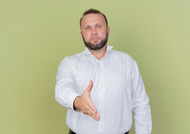 明るい壁の上に立っている手を提供する白いシャツの挨拶を着てひげを生やした男