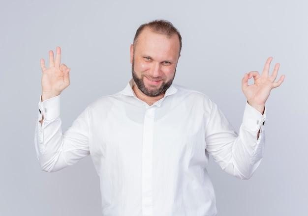 흰 셔츠를 입고 수염 난된 남자가 행복하고 긍정적 인 미소를 짓고 흰 벽 위에 서있는 확인 서명 만들기