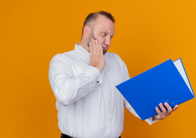 オレンジ色の壁の上に立って驚いて驚いた青いフォルダーを保持している白いシャツを着たひげを生やした男