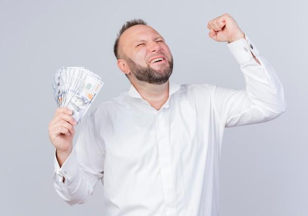현금 떨림 주먹을 들고 흰 셔츠를 입고 수염 난된 남자가 흰 벽 위에 행복하고 흥분된 기쁨 서