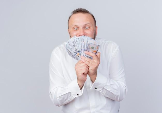 흰색 벽 위에 현금 행복하고 흥분 서 들고 흰 셔츠를 입고 수염 난된 남자