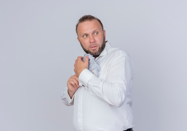 Bearded man wearing white shirt holding cash hiding money looking worried standing over white wall