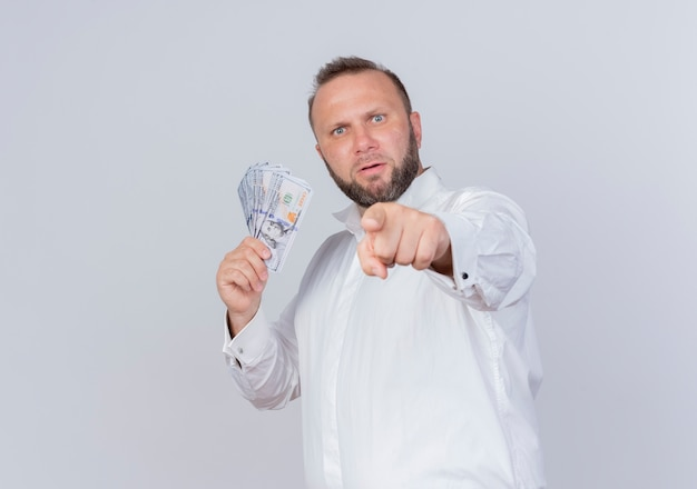 Bearded man wearing white shirt holding cash hiding money  pointign with index finger to you displeased standing over white wall
