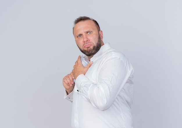 白い壁の上に立っている懐疑的な表現でお金を隠して現金を保持している白いシャツを着たひげを生やした男