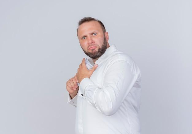 Uomo barbuto che indossa una camicia bianca che tiene contanti nascondendo i soldi con l'espressione scettica in piedi sopra il muro bianco