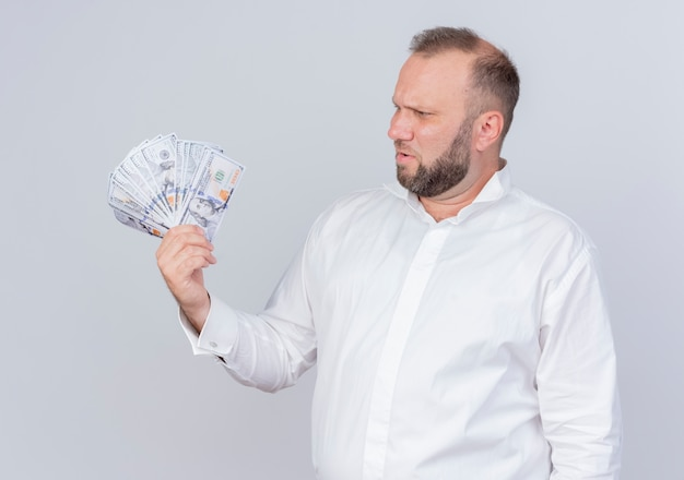 Bearded man wearing white shirt holding cash looking at money with skeptic expression standing over white wall