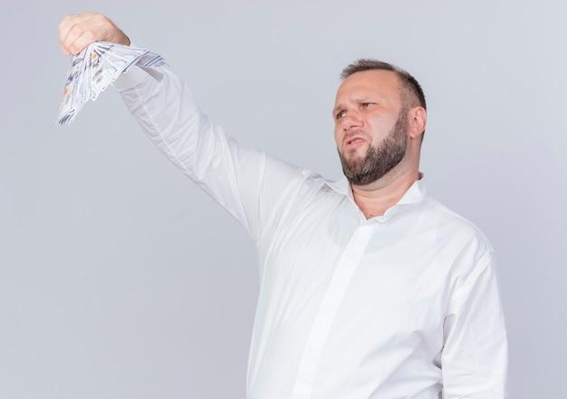 Uomo barbuto che indossa una camicia bianca che tiene contanti guardando soldi con espressione scettica in piedi sopra il muro bianco
