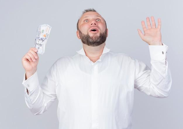 흰색 벽 위에 행복하고 놀란 서 찾고 현금을 들고 흰 셔츠를 입고 수염 난된 남자
