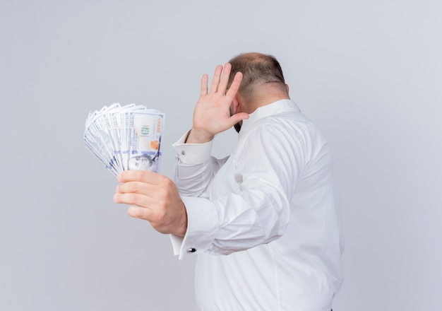 Bearded man wearing white shirt holding cash making defense gesture with hand against money standing over white wall