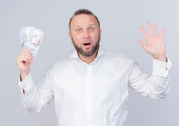 Uomo barbuto che indossa una camicia bianca che tiene i contanti alzando la mano nella resa sorpreso e felice in piedi sopra il muro bianco