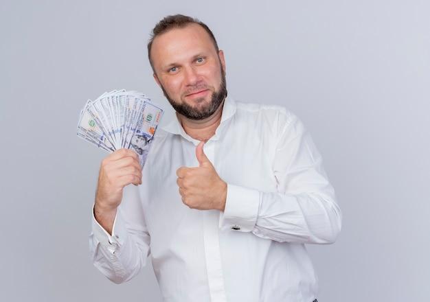 현금을 들고 흰 셔츠를 입고 수염 난된 남자가 흰 벽 위에 서있는 엄지 손가락을 보여주는 미소