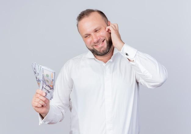 흰 벽 위에 서있는 행복한 얼굴로 웃는 현금을 들고 흰 셔츠를 입고 수염 난된 남자