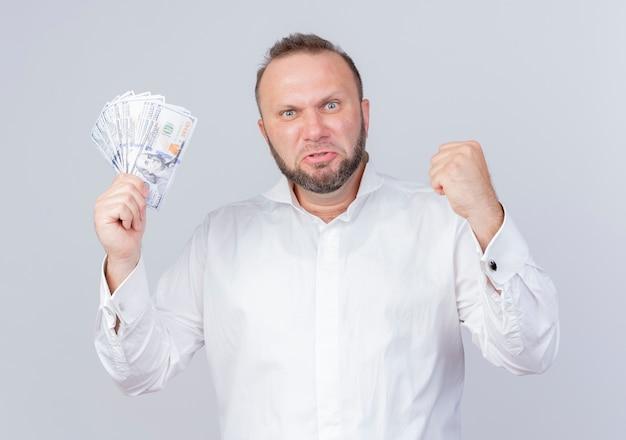 흰 벽 위에 서있는 주먹을 떨리는 화가 얼굴로 현금을 들고 흰 셔츠를 입고 수염 난 남자