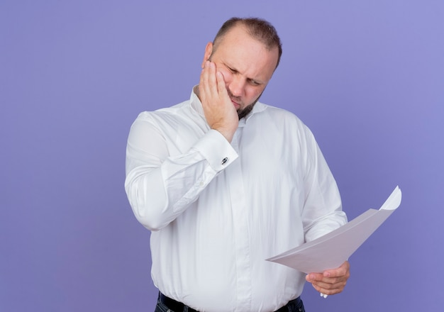 Bearded man wearing white shirt holding documents looking at them puzzled standing over blue wall