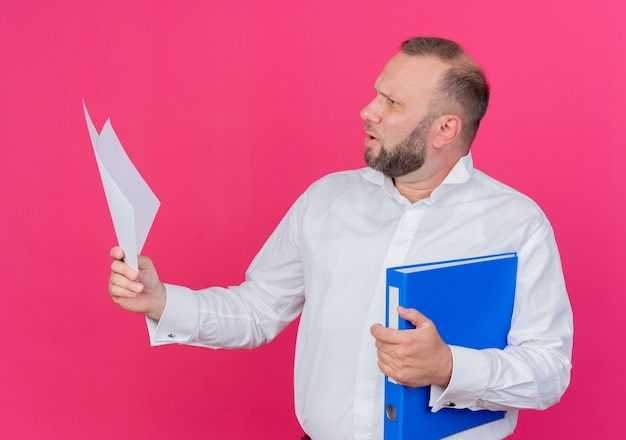 フォルダーと白紙のシートを保持している白いシャツを着ているひげを生やした男はピンクで混乱して脇を見て