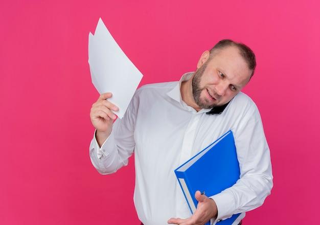 폴더와 문서를 들고 흰 셔츠를 입고 수염 난된 남자가 분홍색을 통해 매우 바쁜 모바일 이야기