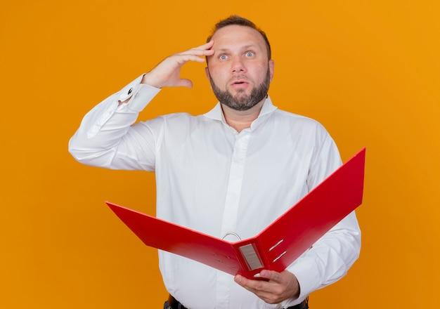 オレンジ色の壁の上に立って困惑して脇を見ているフォルダーを保持している白いシャツを着ているひげを生やした男