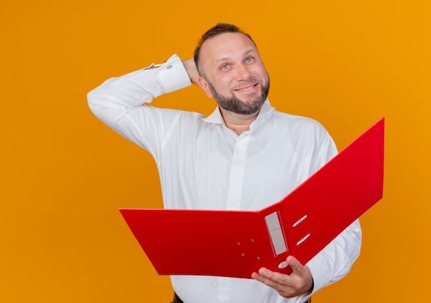 オレンジ色の壁の上に立っている顔に笑顔で脇を見てフォルダーを保持している白いシャツを着ているひげを生やした男