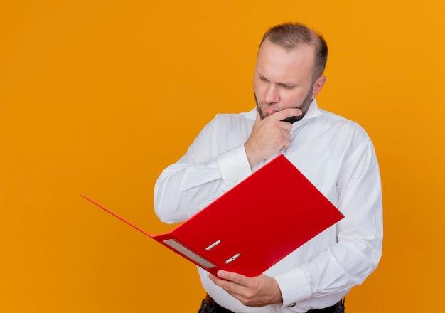 オレンジ色の壁の上に立っている真剣な顔の思考でそれを見てフォルダーを保持している白いシャツを着ているひげを生やした男