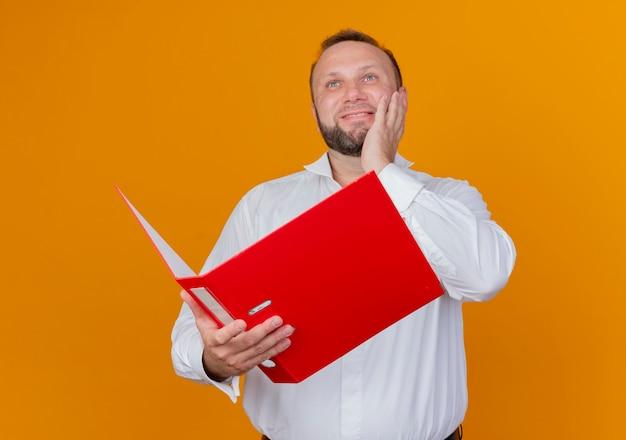 オレンジ色の壁の上に立って笑顔を見上げてフォルダーを保持している白いシャツを着ているひげを生やした男
