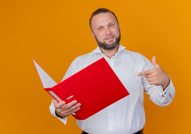 オレンジ色の壁の上に立って微笑んでそれを指で指しているフォルダを保持している白いシャツを着ているひげを生やした男