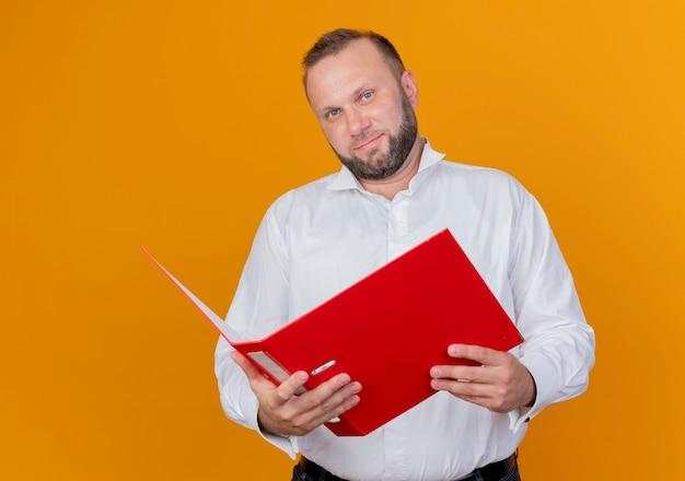 オレンジ色の壁の上に立って笑顔のフォルダーを保持している白いシャツを着ているひげを生やした男