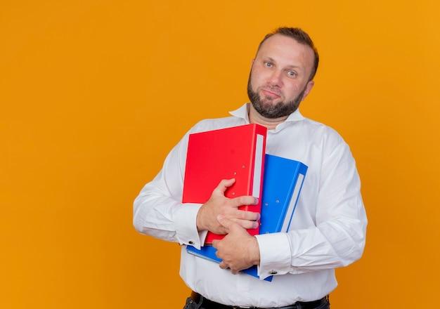 Uomo barbuto che indossa una camicia bianca che tiene le cartelle confuse con l'espressione triste in piedi sopra la parete arancione