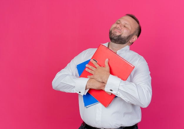 Bearded man wearing white shirt holding folders feeling thankful and poisitve emotions with closed eyes over pink