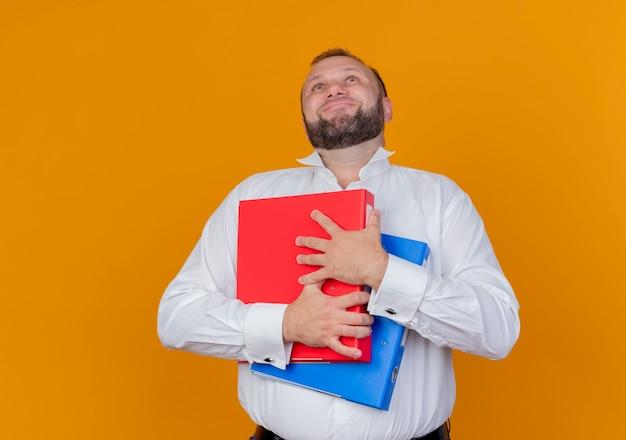 Uomo barbuto che indossa una camicia bianca che tiene le cartelle lookign con la faccia felice in piedi sopra la parete arancione