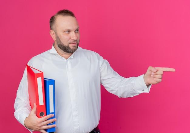 Uomo barbuto che indossa una camicia bianca che tiene le cartelle guardando da parte pointign con il dito indice a qualcosa di rosa