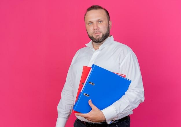 Uomo barbuto che indossa una camicia bianca che tiene le cartelle con la faccia seria in piedi sopra il muro rosa