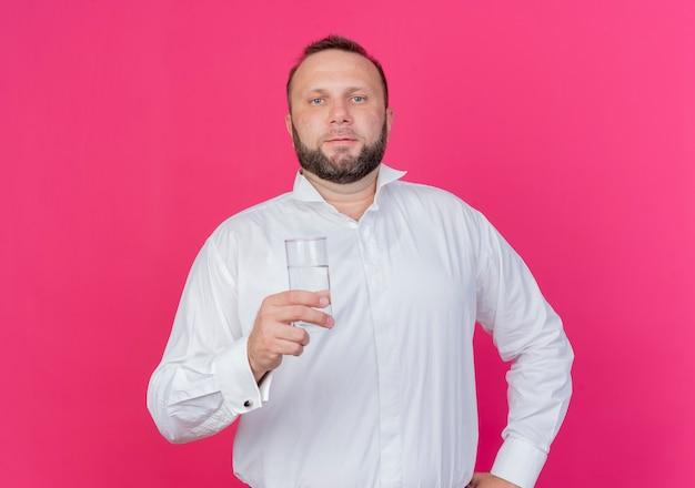 분홍색 벽 위에 서 심각한 얼굴로 물 잔을 들고 흰 셔츠를 입고 수염 난된 남자